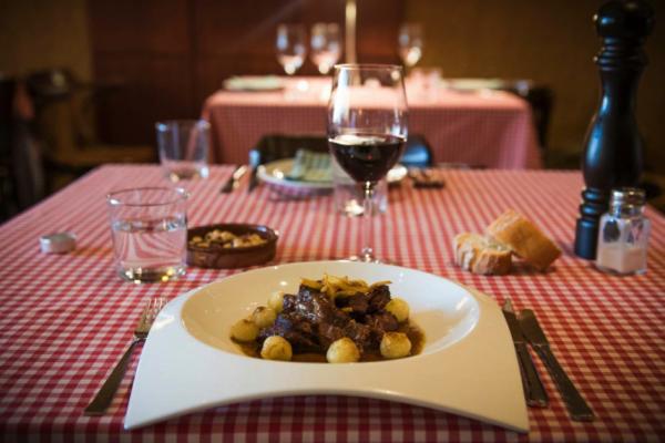 Ochsenschwanz mit kleinen Zwiebeln von einem guten Rotwein begleitet